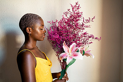 Woman in yellow dress smelling flowers by white wall at home - p300m2241633 by Rafa Cortés