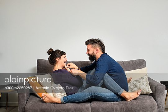 Adult couple sitting together on sofa - p300m2250287 by Antonio Ovejero Diaz