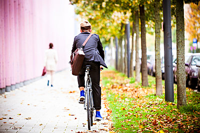 Young businessman riding bicycle, Munich, Bavaria, Germany - p1026m991987f by Dario Secen