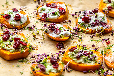 Slices of sweet potato with cream cheese, ramson cream, goat cheese, cress and cranberries - p300m1581215 von Sandra Roesch