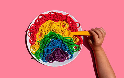 Hand of baby girl eating rainbow-colored spaghetti - p300m2198264 by Gemma Ferrando