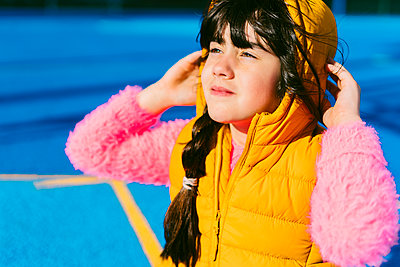 Cute girl in warm clothing looking away while sitting on sports court - p300m2226006 by Eloisa Ramos