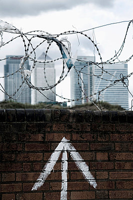 Brick wall with barbed wire on top, plastic bags caught on barbs, Canary Wharf in background; Greenwich Peninsula, London, UK  - p442m839968 by Naki Kouyioumtzis