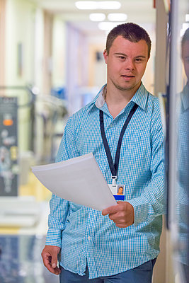 Caucasian man with Down Syndrome holding paperwork in hospital  - p555m1305980 by Disability Images