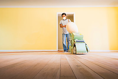 Hispanic man refinishing floors in new house - p555m1408522 by Sollina Images