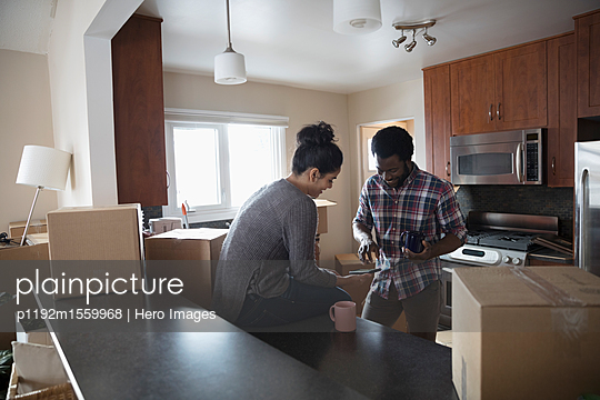 Young couple moving into new house, taking coffee break and using smart phones in kitchen - p1192m1559968 by Hero Images