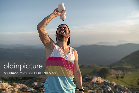 Athlete pouring water on face while standing on mountain against clear sky - p300m2227173 by SERGIO NIEVAS