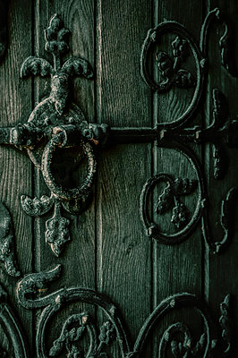 Close-up of an old wooden church door with decorative metalwork and handle - p1047m1031587 by Sally Mundy