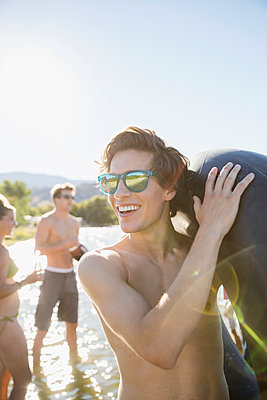 Smiling young man wearing sunglasses holding inner tube at sunny summer lake - p1192m1183775 by Hero Images