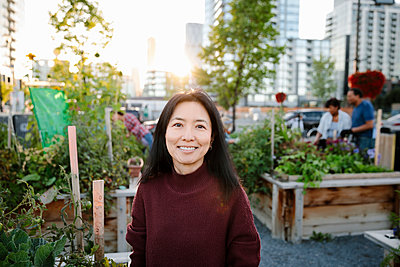 Portrait happy woman in urban community garden - p1192m2130128 by Hero Images