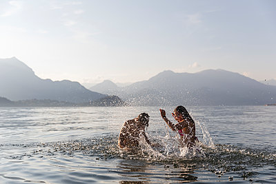 Happy young couple playing in a lake - p300m2042937 von Michela Ravasio