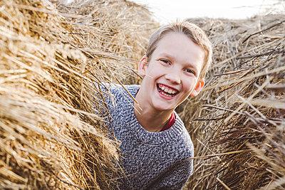 Cheerful boy peeking from haystack - p300m2225487 by Ekaterina Yakunina
