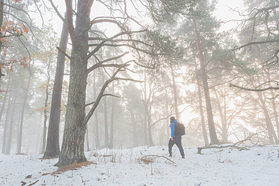 A man walking through a snowy forest - p352m1523751 by Calle Artmark