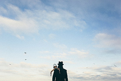 Drone on shoulder of man watching birds fly - p555m1303697 by Sophie Filippova