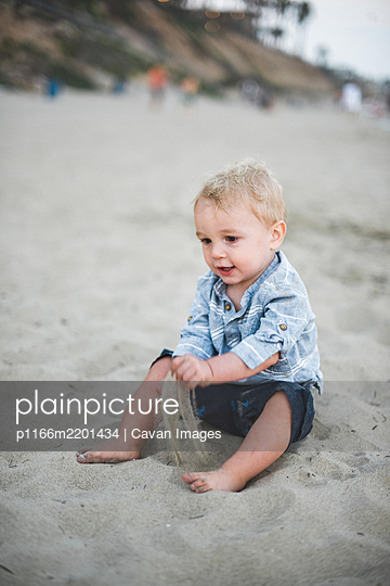 Little boy playing with sand on a California beach - p1166m2201434 by Cavan Images