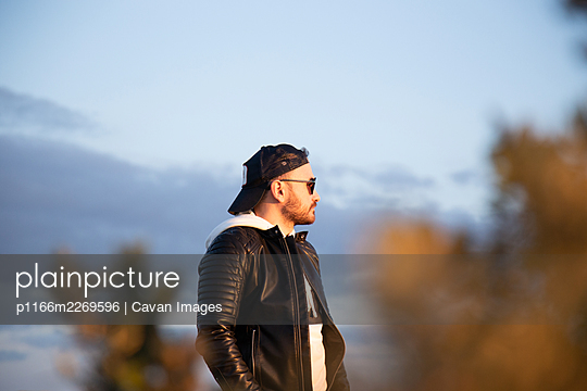 Man with sunglasses, dark cap, fur jacket and white sweatshirt, lookin - p1166m2269596 by Cavan Images