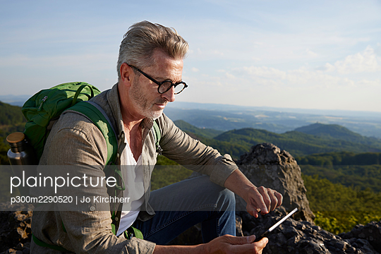 Male hiker using digital tablet while sitting on mountain - p300m2290520 by Jo Kirchherr
