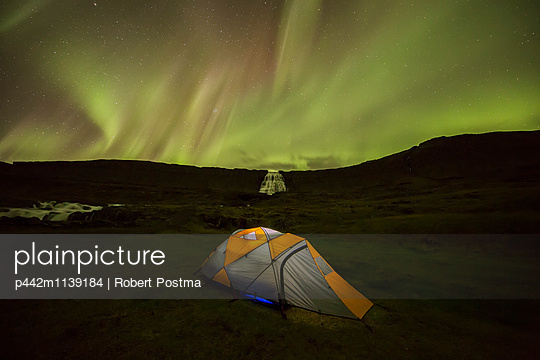 Tent lit up at night in front of the waterfall Dynjandi; West Fjords, Iceland - p442m1139184 by Robert Postma
