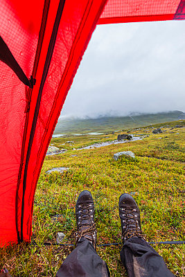 Hiker resting in tent - p312m974958f by Mikael Svensson