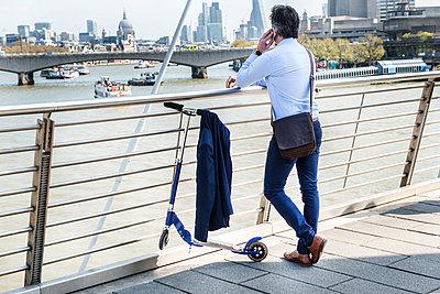 Businessman beside scooter, Hungerford Bridge, London, UK - p429m1418037 by Bonfanti Diego