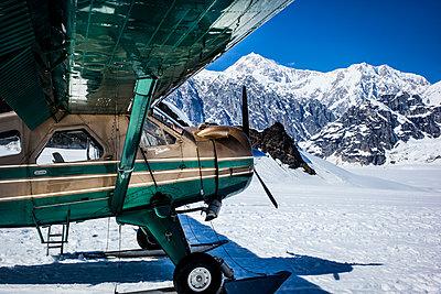 Propellerflugzeug vor schneebedeckter Bergkette, Alaska - p741m2168712 von Christof Mattes