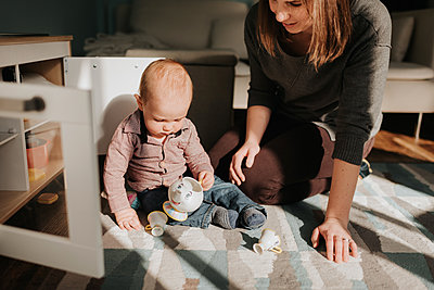 Mother playing with baby son on living room rug - p924m2077730 by Sara Monika