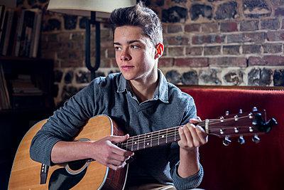 Boy playing guitar - p940m1132358 by Bénédite Topuz