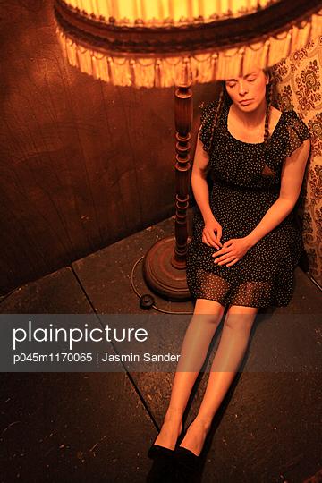 Traurige Frau unter Lampenschirm - p045m1170065 von Jasmin Sander