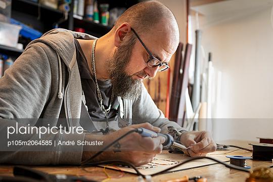 Bastler lötet in einer Werkstatt - p105m2064585 von André Schuster