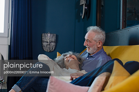 Happy senior couple resting on sofa at home - p300m2265907 by Emma Innocenti