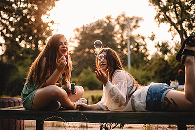 Happy lesbian couple playing with bubbles relaxing in park in summer - p1166m2212492 by Cavan Images