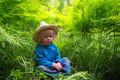 Little boy in straw hat sitting in grass - p1418m2014909 by Jan Håkan Dahlström