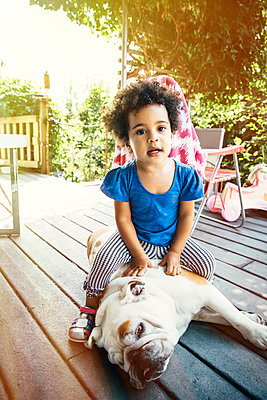 Mixed race girl sitting on dog on porch - p555m1421592 by Inti St Clair