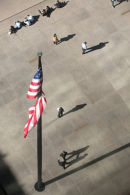 USA flag and pedestrians in New York City - p919m1355154 by Beowulf Sheehan
