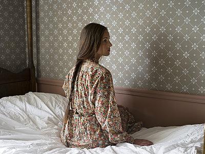 Junge Frau sitzt auf dem Bett - p945m1154634 von aurelia frey