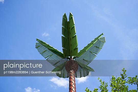 Artificial palm tree against blue sky - p1198m2283894 by Guenther Schwering
