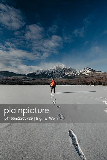 Mann steht auf zugefrorenem See - p1455m2203729 von Ingmar Wein