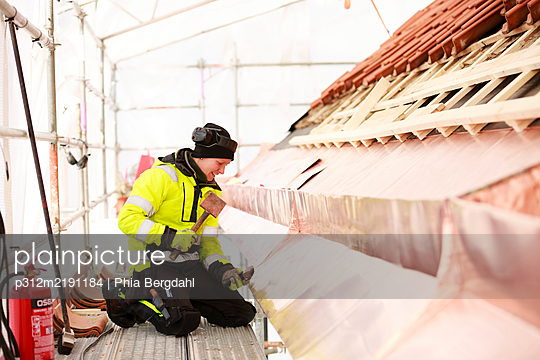 Woman working on roof - p312m2191184 by Phia Bergdahl