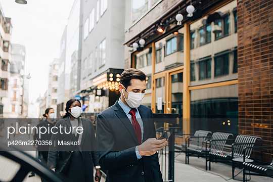 Businessman using smart phone while female colleagues social distancing in city during pandemic - p426m2270356 by Maskot