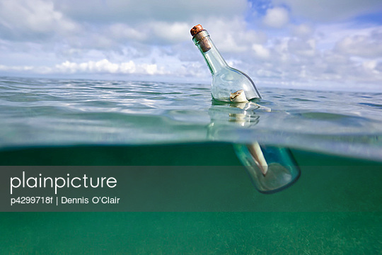 Message in a bottle floating in ocean - p4299718f by Dennis O'Clair