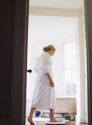 Mature woman in bathrobe stepping on bathroom scale - p1023m1577424 by Sam Edwards