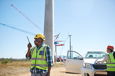 Male engineer with walkie-talkie at sunny wind turbine power plant - p1023m1583994 by Trevor Adeline