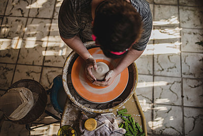 High angle view of female craftsperson making clay pot at pottery - p1166m1512987 by Cavan Images
