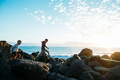 Playful brothers running on rocks against sky at beach - p1166m1546854 by Cavan Images