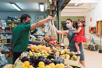 A young woman with a mask shopping at the fruit shop with her daughter - p1166m2212451 by Cavan Images