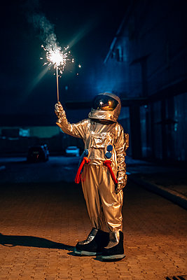Spaceman standing outdoors at night holding sparkler - p300m2043139 by Vasily Pindyurin