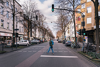 Man with mask walking in the middle of an empty street in the city - p300m2170604 by Mareen Fischinger