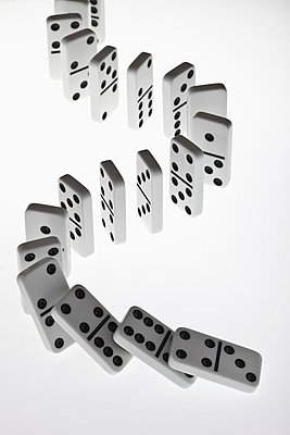 Dominoes in a row, beginning to fall over in a chain reaction - p301m730776f by Larry Washburn
