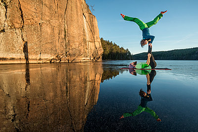Couple doing yoga on frozen lake - p312m1471875 by Fredrik Schlyter