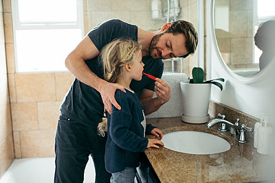 Mid adult father brushing daughter's teeth at sink in bathroom - p426m1451772 by Maskot